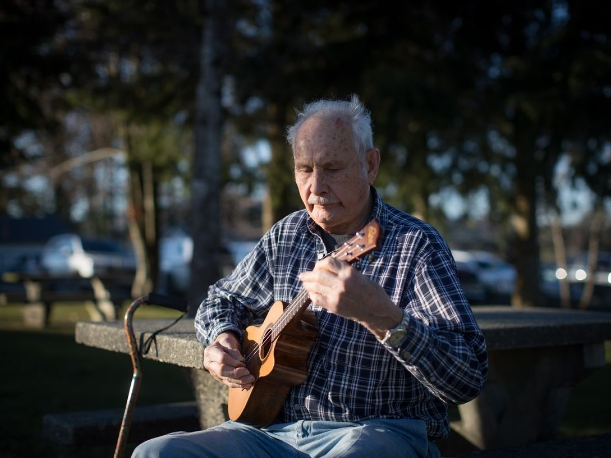 elderly man playing the guitar